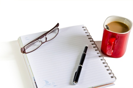 Notebook, pen, coffee red cup on the isolated background photo