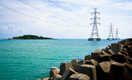 High voltage power pole in the sea and rock photo