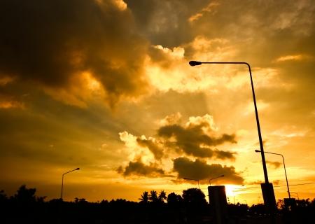 lamp on the pole: Street lamp in orange sky at dawn Stock Photo