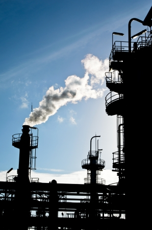 silhouette of smoking smokestack in petrochemical plant
