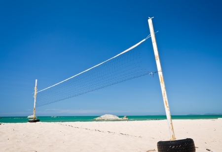 A beach volleyball net on a sunny day with blue sky