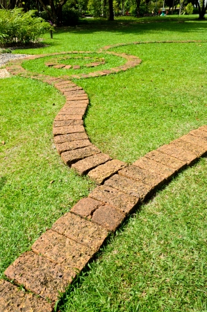 The stone block walk path in the garden with green grass Stock Photo