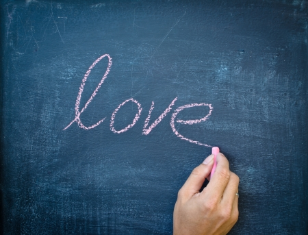 Writing love with chalk on black board photo
