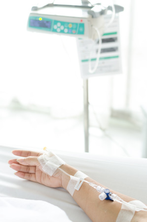 morphine: IV solution in a patient hand and IV machine