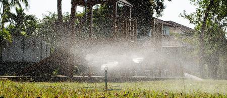 sprinkler watering on lawn play ground