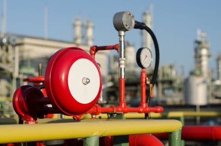 fire protection: red fire alarm and petrochemical plant background Stock Photo