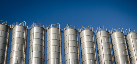 silos: Industrial silos in the chemical industry and blue sky background