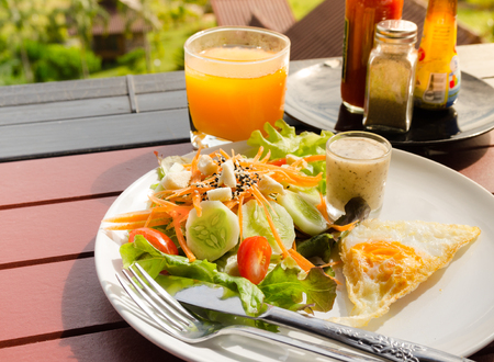 vegetable salad with fried egg,orange juice  healthy breakfast Stock Photo