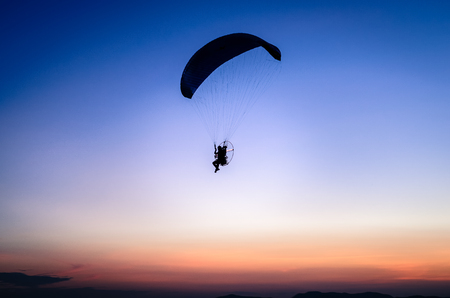 Paraglide silhouette flying at dawn