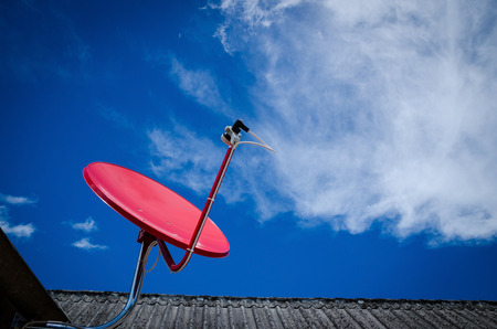 Red Satellite TV Receiver Dish on the Old Tiles Roof