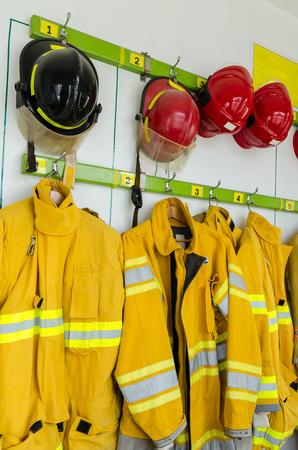 casco rojo: Trajes de bombero y cascos que cuelgan en la estación de bomberos Foto de archivo