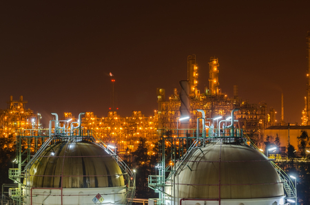 sphere gas tank with petrochemical plant background at night