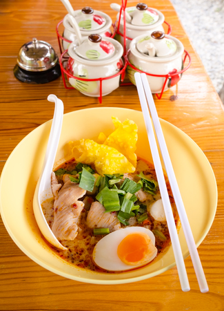 bowl of  delicious noodles with vegetables and boiled egg on wooden table,thai noodles spicy