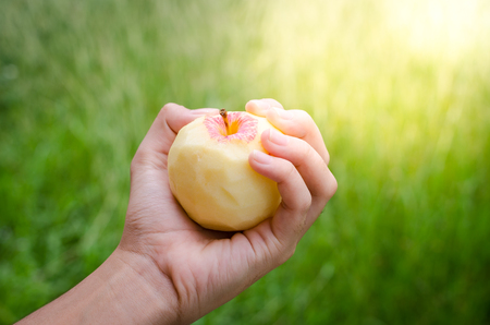 A red apple on hand , selective focus , blurred grass background