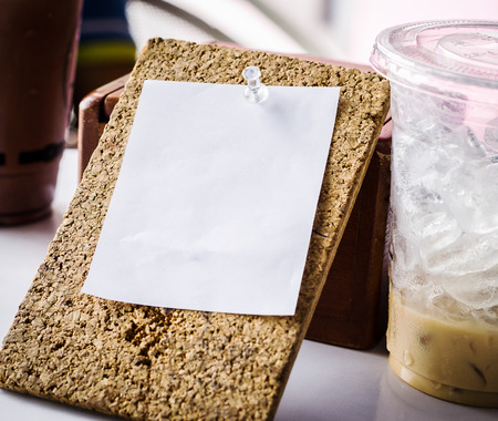 note board: white note paper on cork board with cold baverage glass