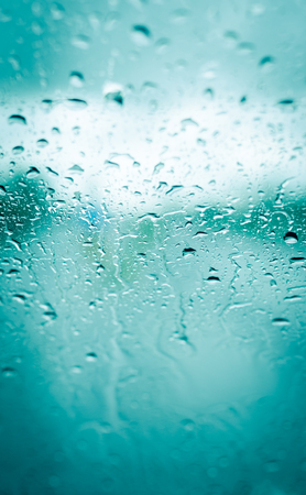 heavy rain drops on front car green glass