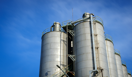 steel tower: silos in petrochemical plant with blue sky background Stock Photo