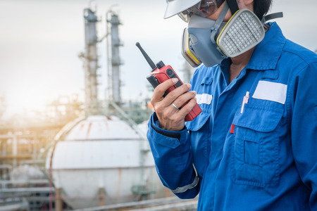 technician with gas mask against petrochemical plant background  communicate by walkie-talkie Archivio Fotografico