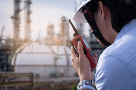 Industrial engineer working in field the petrochem plant with talking on the walkie-talkie for controlling work Stock Photo