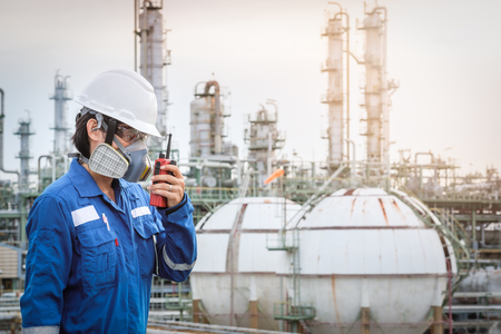 technician with gas mask against petrochemical plant background  communicate by walkie-talkie Standard-Bild