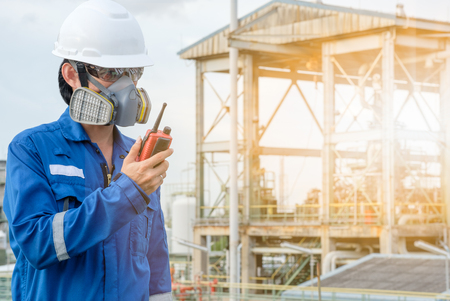 technician with gas mask against petrochemical plant background  communicate by walkie-talkie Stock Photo