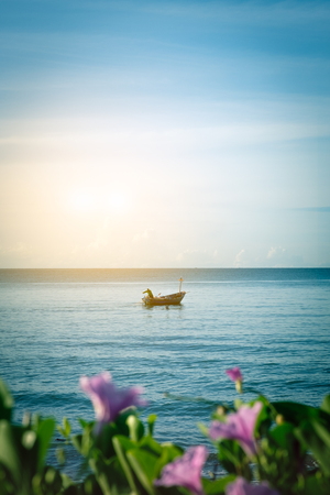 pes caprae: fisherman and fishing boat in morning time with blur ipomoea pes-caprae foreground