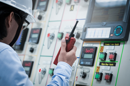 Industrial engineer working operated control panel with talking on the walkie-talkie for controlling work Stock Photo