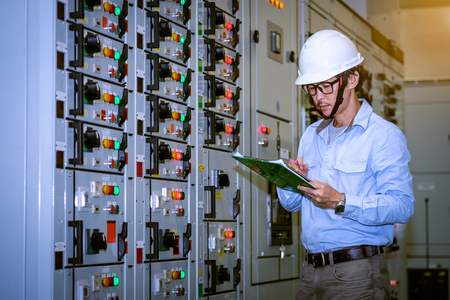 industrial technician check voltage or current status in control panel of power plant. Stock Photo