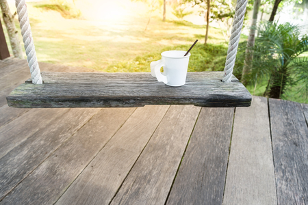 morning coffee cup on wood swing in green garden space ,relax time