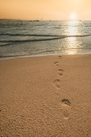 beach, wave and footprints at sunrise time,Footprints in the sand at sunset Stock Photo