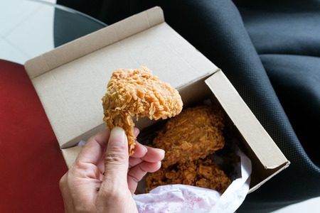 hand hold deep fried chicken from paper box 写真素材