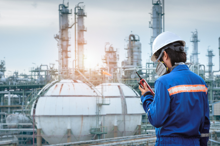 technician stand with gas mask against petrochemical plant background communicate by walkie-talkie