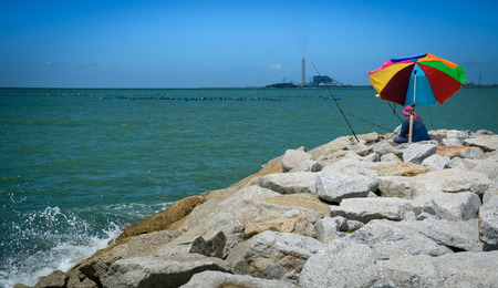 Fisherman and colourful umbrella on rock coast with industrial plant background