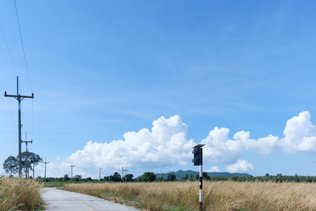 elctric pole on blue sky in countryside, power lines pass through green and yellow fields.
