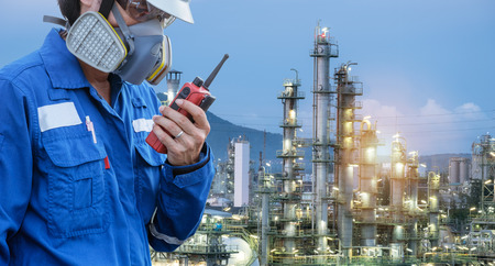 technician with gas mask against petrochemical plant background communicate by walkie-talkie