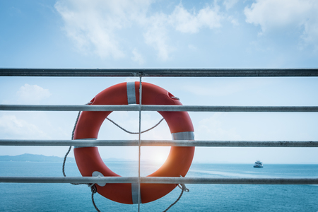 Close-up orange lifebuoy ring hanging on ferry boat with ocean background Stockfoto