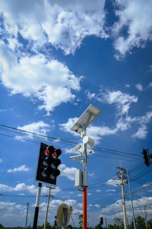 Security camera at the traffic light pole with beautiful blue sky as background