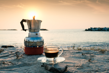 hot esspresso shot or hot black coffee from mokka pot  ready to serve at freshy morning time on the beach outdoor activity.black coffee ready to drink from mug on the beach outdoor picnic. Standard-Bild