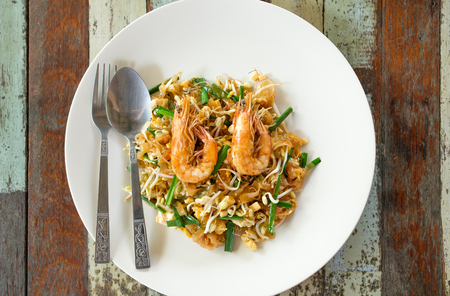 Fried noodle Thai style with prawns. On wood table. Top view Pad Thai with shrimps, Thailand national dish