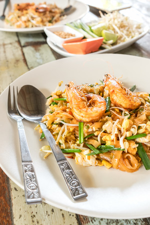 Fried noodle Thai style with prawns. On wood table. Top viewPad Thai with shrimps, Thailand national dish