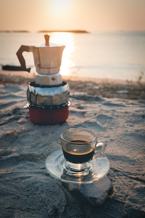 hot esspresso shot or hot black coffee from mokka pot  ready to serve at freshy morning time on the beach outdoor activity.black coffee ready to drink from mug on the beach outdoor picnic. Stockfoto