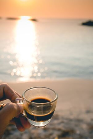 Closeup hand hold coffee cup on sand beach and view of sunset or sunrise background,peaceful,black coffee ready to drink from mug on the beach outdoor picnic. Stockfoto