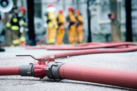 red fire hose equipment connected and open valve for fire fighting team.red fire hose and fire man background.