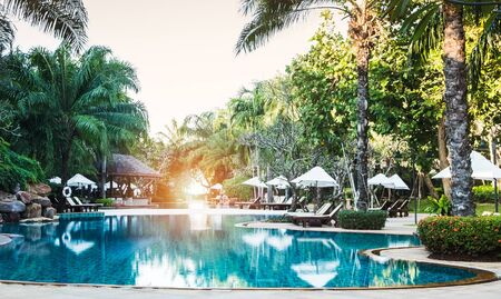 swimming pool in tropical resort.swimming pool with palm tree and bed for relax. Standard-Bild