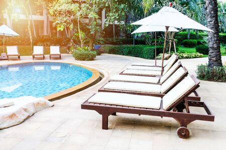 Relaxing pool bed beside swimming pool in tropical resort.