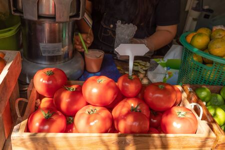 Red ripe tomatoes in basket prepare to do tomato juice for sale at market in Thailand.