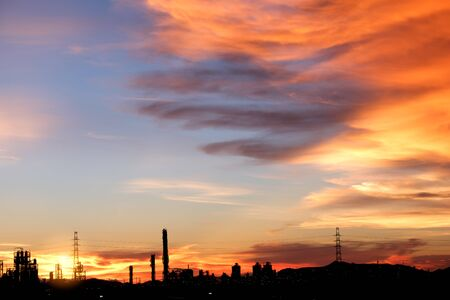 Beautiful dramatic sunset with silhouette the factory . Atmospheric industrial evening view.  Silhouette factory with beautiful sky background.