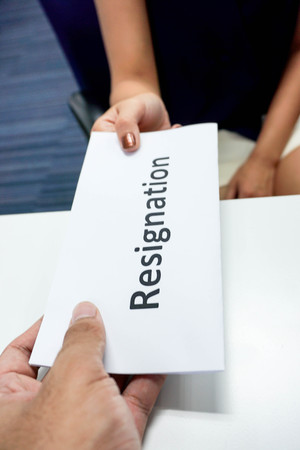resignation: Close up submitting a resignation letter to the boss