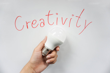 Concept wording of creativity with LED bulb in hand Stock Photo