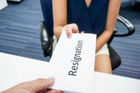 A woman submit a resignation letter to her boss Stock Photo